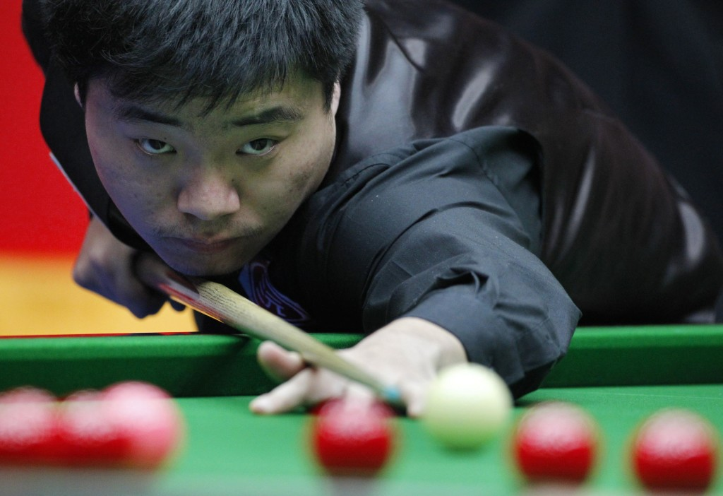 China's Ding plays a shot during his match against Williams of Wales in the final of the 2010 World Snooker China Open in Beijing