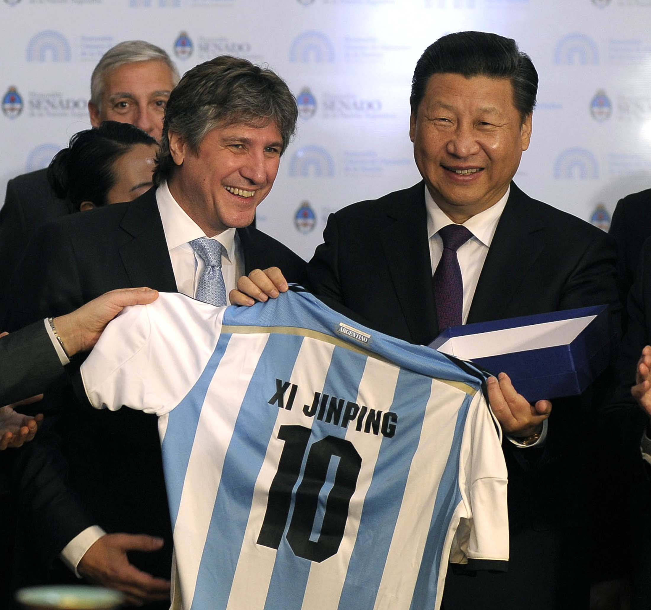 China s president xi jinping receives an argentine soccer jersey with his name on it from argentina s